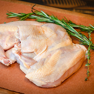Uncooked semi-boneless half chicken on butcher paper with rosemary and thyme springs.