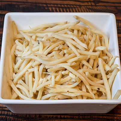 Par cooked french fries in a square white bowl.