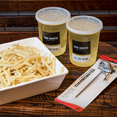 French Fry Kit including two quart containers of frying oil, a deep fry thermometer, and a square bowl of par cooked french fries.