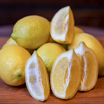 Six lemons, one of which is quartered.