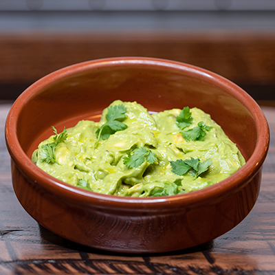 Guacamole garnished with cilantro served in a terracotta bowl.