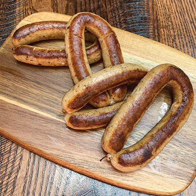 Four links of breakfast sausage on a wood cutting board.