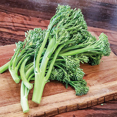 Five stems of raw broccolini on a wood cutting board.