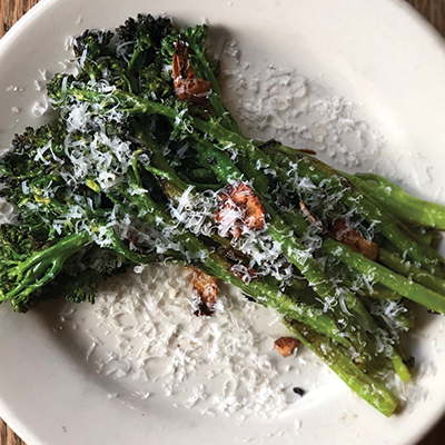 Roasted broccolini garnished with parmesan cheese and fried garlic on a white plate.
