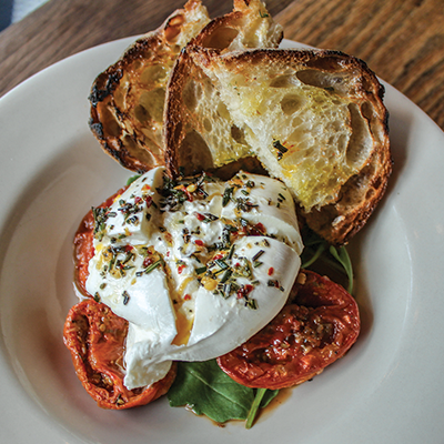 Burrata cheese on top of spinach and roasted tomatoes with grilled bread on the side served on a white plate.