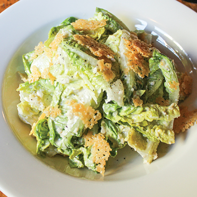 Little gem caesar salad served in a white plate topped with parmesan frico.