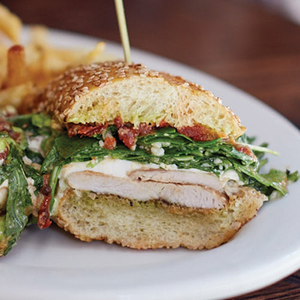 Grilled chicken sandwich with arugula, burrata and slow roasted tomatoes on a sesame bun served on a white plate.