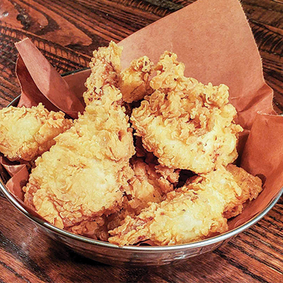 Chicken tenders in a basket lined with butcher paper.