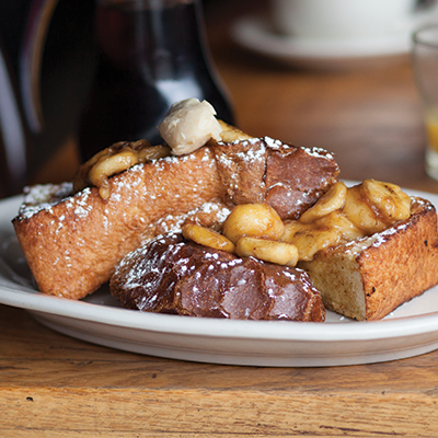 Vanilla Bean French Toast topped with caramelized bananas, maple butter, and powdered sugar on a white plate.