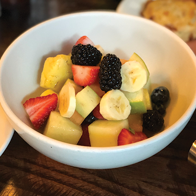 Fruit salad with blackberries, bananas, strawberries, blueberries, melon and pineapple in a white bowl.