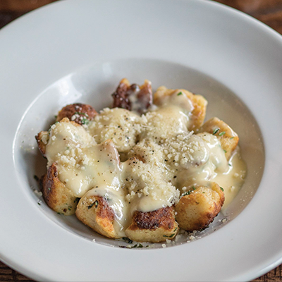 Toasted ricotta gnocchi with truffle cream garnished with grated parmesan cheese and parsley served in a white bowl.