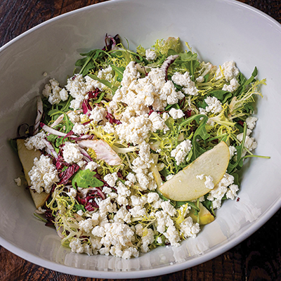 Salad of mix greens in a bowl with crumbled goat cheese.