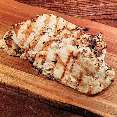 Three grilled chicken cutlets on a wood board.
