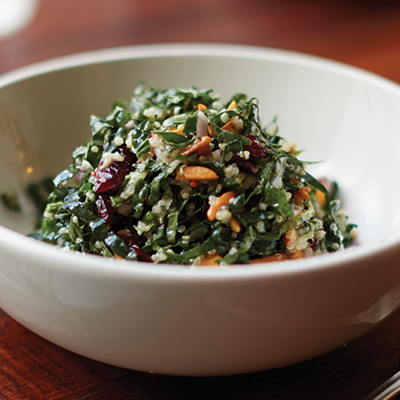 Kale and quinoa salad with dried cranberries and toasted almonds served in a white bowl.