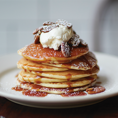 Stack of pancakes topped with whipped ricotta, toasted pecans, salted caramel sauce, and powdered sugar on a white circular plate.