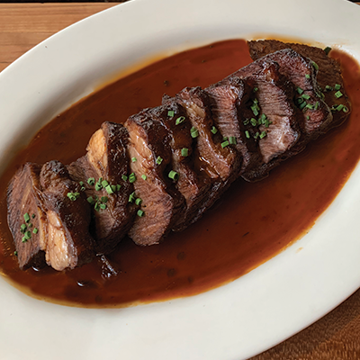 Braised beef short ribs, sliced and presented on a white oval plate with jus.