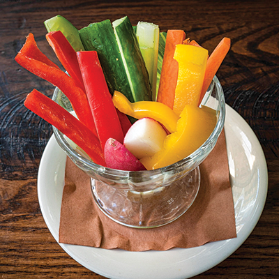 Sliced vegetable crudités including peppers, cucumber, carrot and radish served in a glass dish on a white plate.