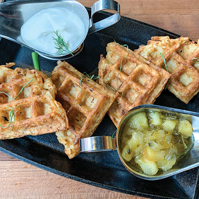 Potato Latke Waffles on a cast iron pan garnished with dill and served with sour cream and apple chutney.