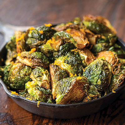 Roasted brussels sprouts with orange zest and sea salt in a small circular cast iron pan.