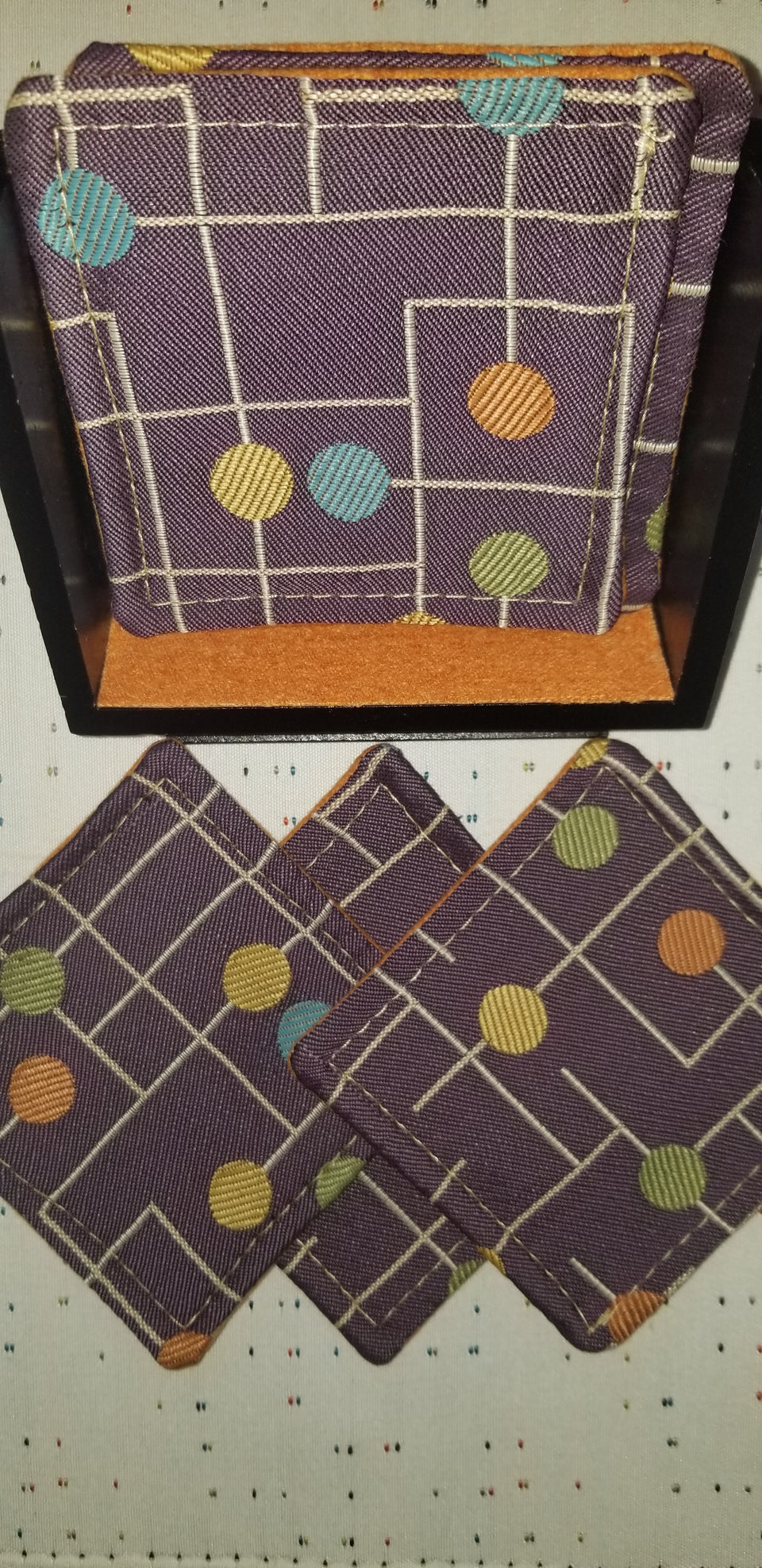 modern walnut pedestal coaster holder with purple and orange fabric coasters