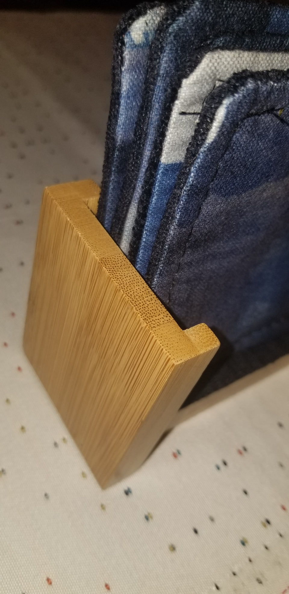 Modern bamboo upright coaster holder with blue velour lining with matching Chase coasters side detail.