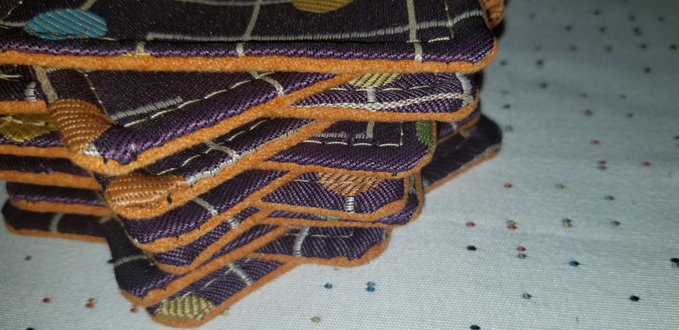 Stack of purple, yellow, blue, and orange geometric patterned coasters called Carmine side detail 2
