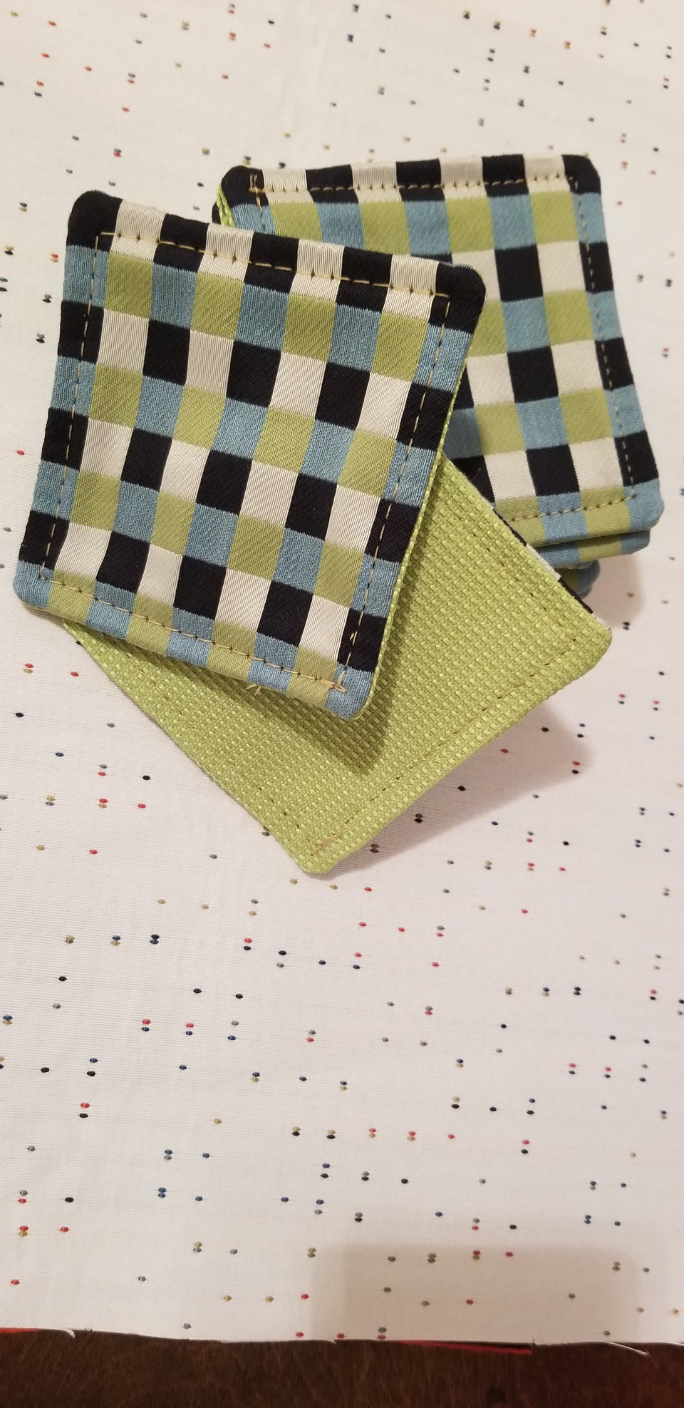 Chuck black, white, lime green, and turquoise gingham check patterned coasters front back detail top view.
