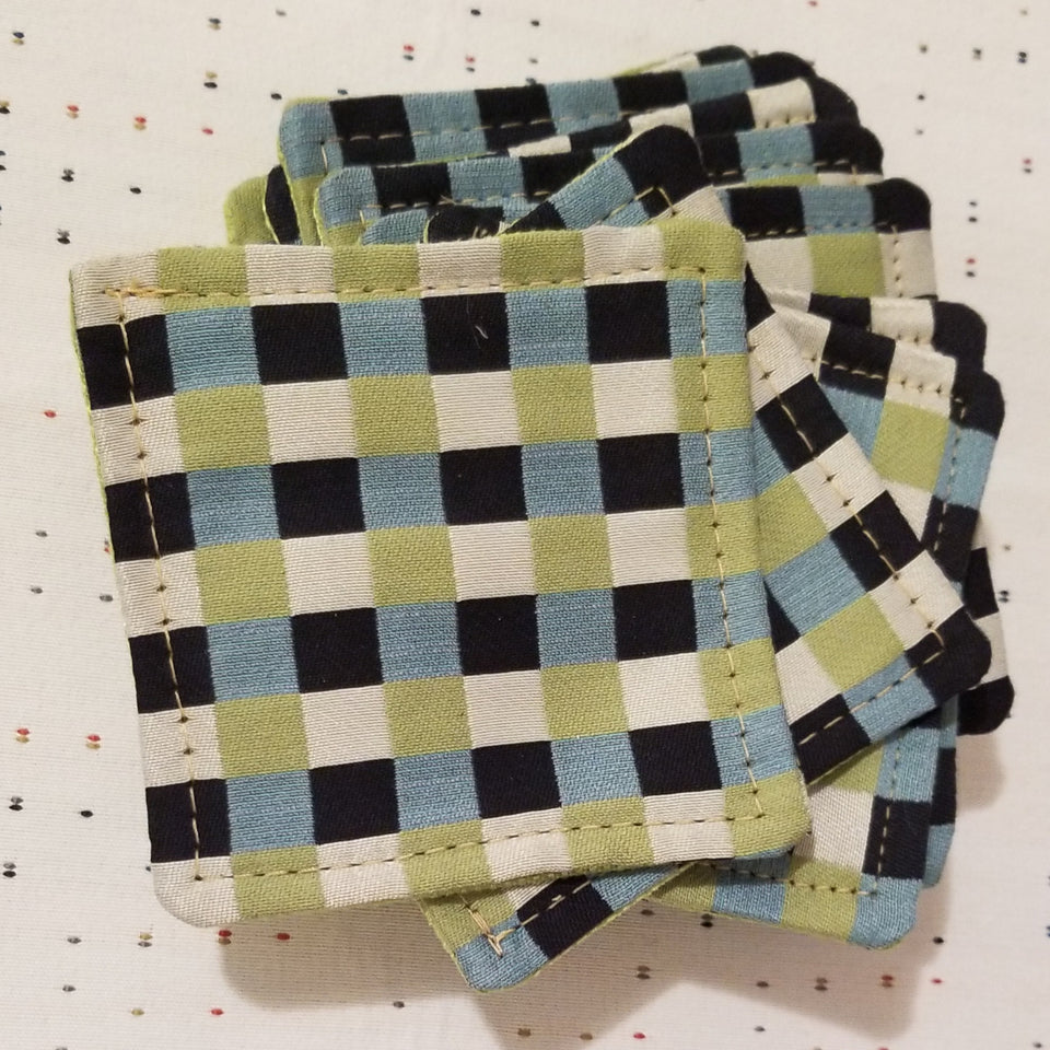 Stack of Chuck black, white, lime green, and turquoise gingham check patterned coasters detail top view.