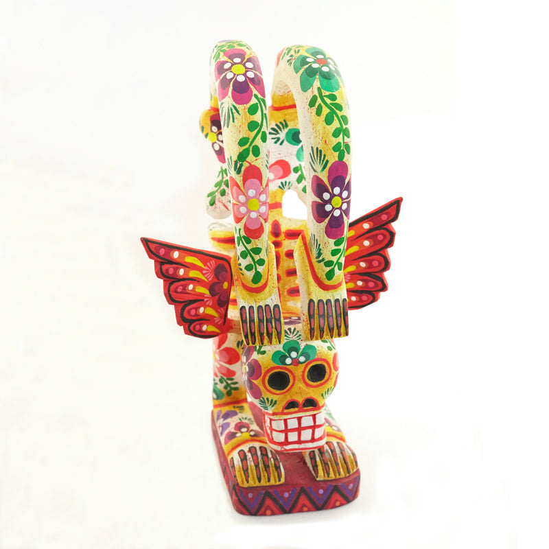 Handmade colorfully painted pine wood standing skeleton figurine with wings. Its feet are bent backwards over its head. Perfect for Day of the Dead and Halloween.