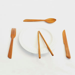 Reusable wooden cutlery set made of mahogany, including a fork, spoon, knife, and two chopsticks. They are on a white plate.