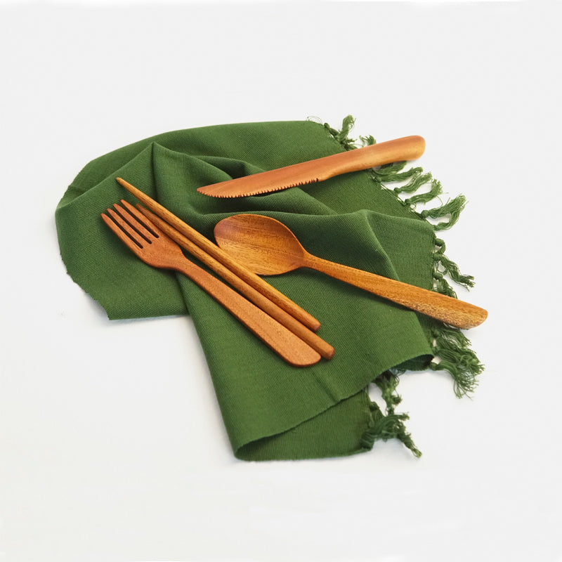 Reusable wooden cutlery set made of mahogany, including a fork, spoon, knife, and two chopsticks. They are on a green napkin.