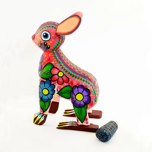 Removable tail next to its colorful standing painted wooden rabbit figurine with floral details