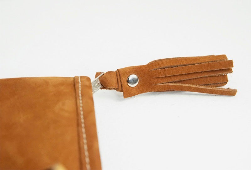 The leather fringe detail on the zipper of a large handmade leather bag with white and black-striped cotton fabric, leather handles and an adjustable strap.