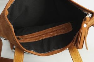 The black cotton lining and inner pocket with zipper in a large handmade leather bag with white and black-striped cotton fabric, leather handles and an adjustable strap.