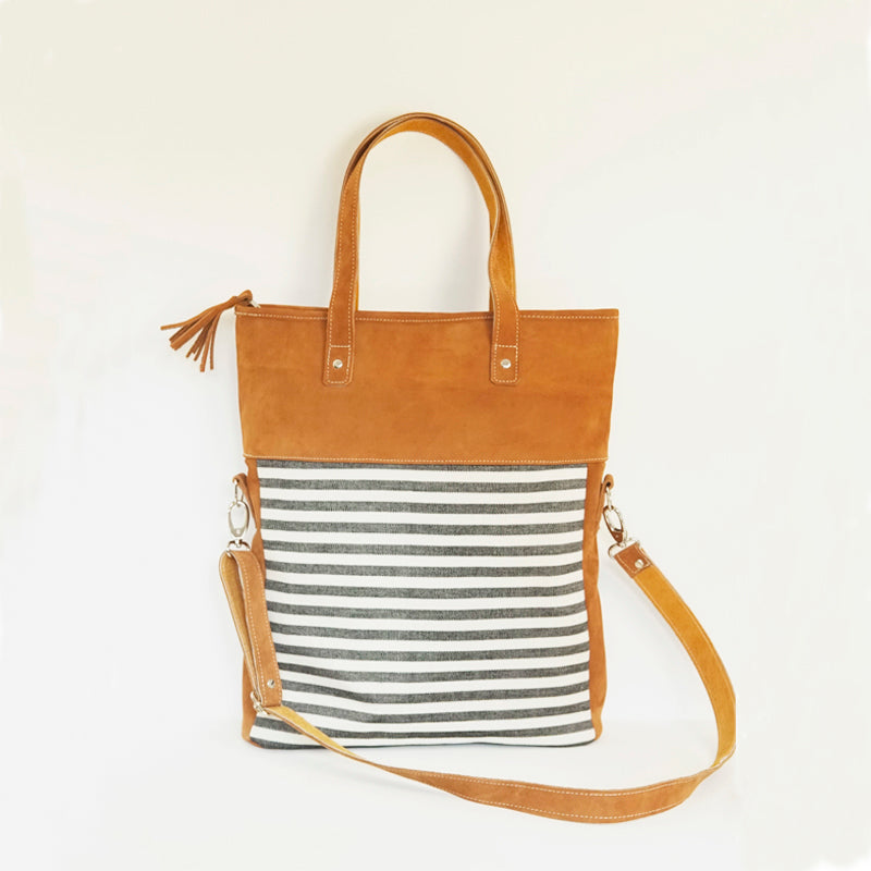 A large handmade leather bag with white and black-striped cotton fabric, leather handles and an adjustable strap.