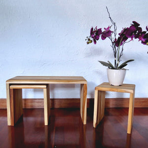 One large light-colored nesting bench with two smaller nesting benches made of sustainable teak wood.