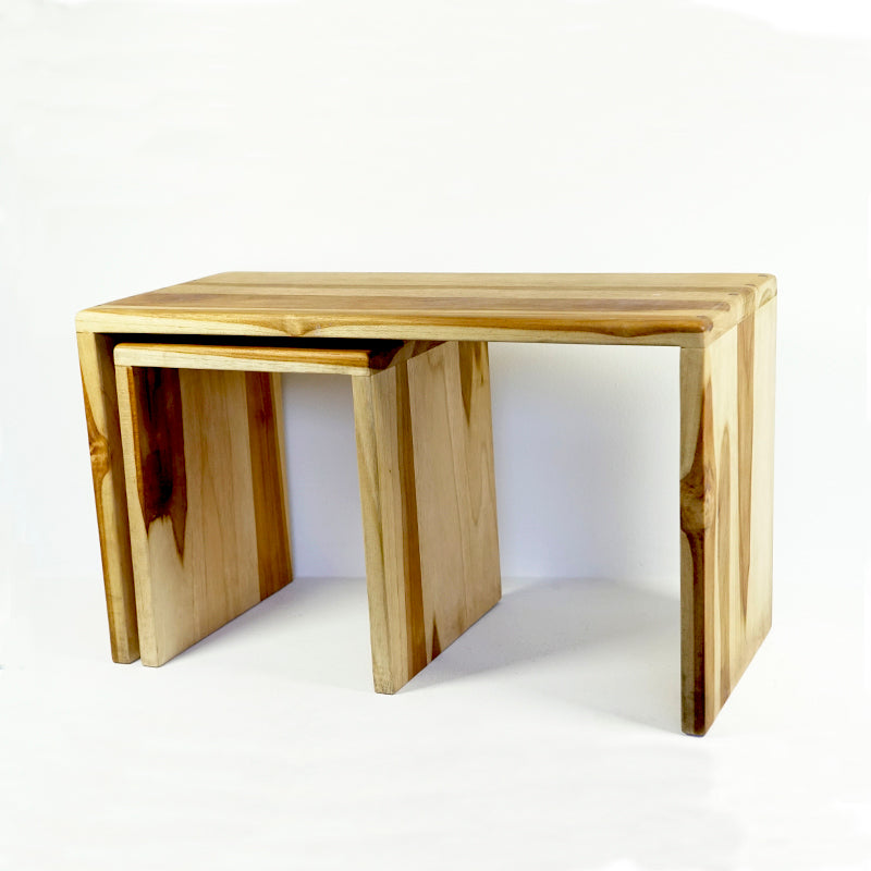One long light-colored nesting bench with a small nesting bench underneath it made of sustainable teak wood.