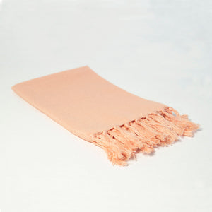Reusable peach pink cloth napkin handwoven by Guatemalan artisans out of 100% cotton with a fringe along one edge