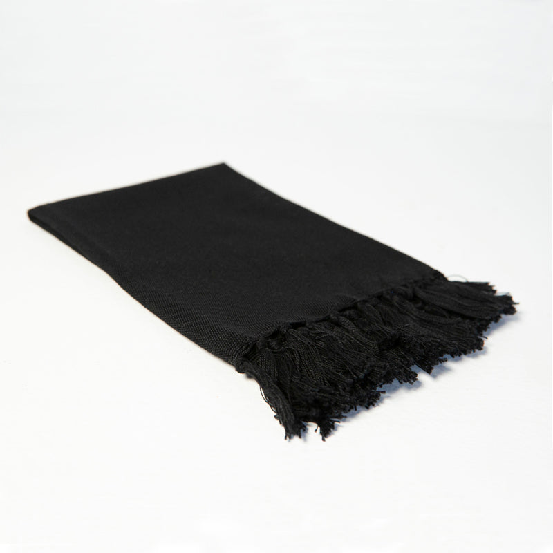 Reusable black cloth napkin handwoven by Guatemalan artisans out of 100% cotton with a fringe along one edge