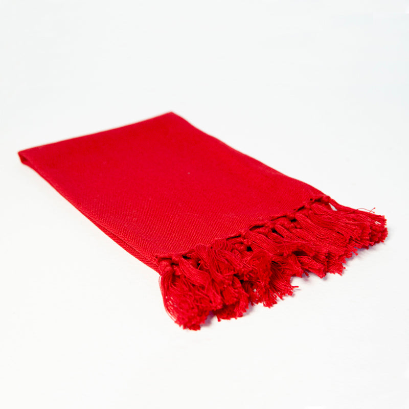 Reusable bright red cloth napkin handwoven by Guatemalan artisans out of 100% cotton with a fringe along one edge