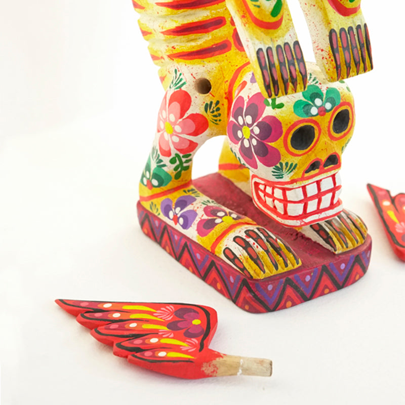 Handmade colorfully painted pine wood standing skeleton figurine with removable wings. Its feet are bent backwards over its head. Perfect for Day of the Dead and Halloween. It has a yellow background and red and green floral details.