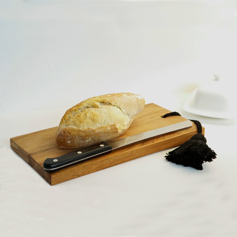 A cutting board made of conacaste wood with a baguette and knife on it. The board has a black cotton tassel on one end.