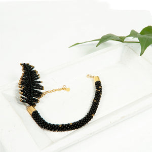 A beautiful handmade black beaded bracelet with a feather charm, extender chain, and lobster clasp