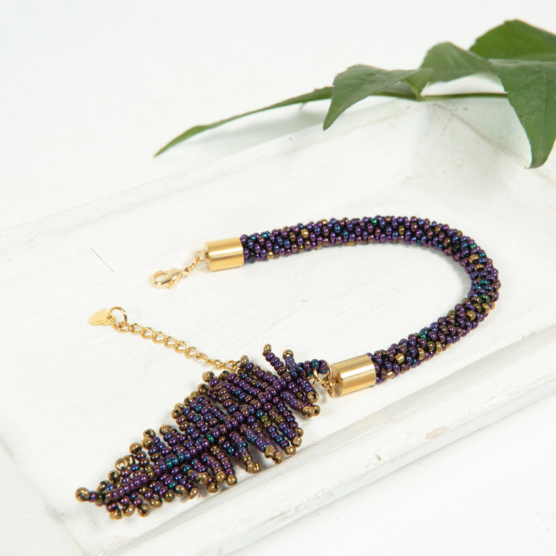 Handmade purple beaded bracelet with a feather charm, extender chain, and lobster clasp