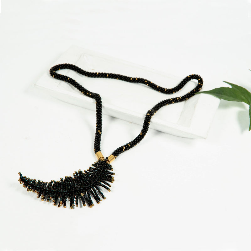 A black and gold-colored seed bead necklace with a beaded feather charm that is handmade by local Guatemalan artists.