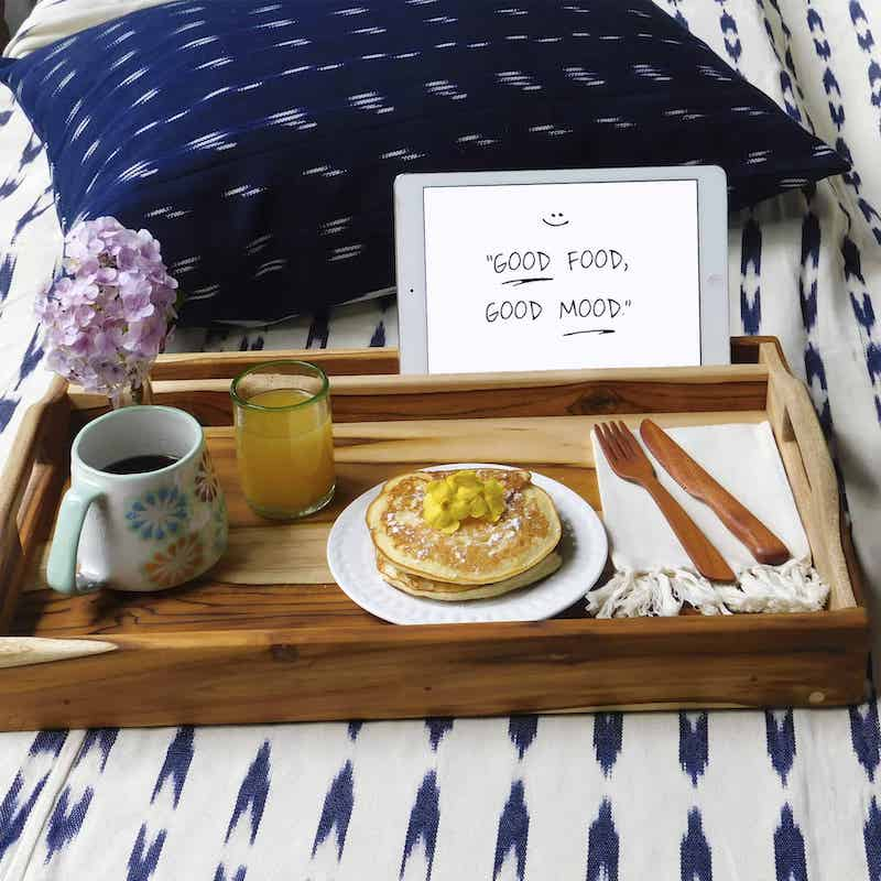 Breakfast tray with food and folded legs on a blue and white bedspread