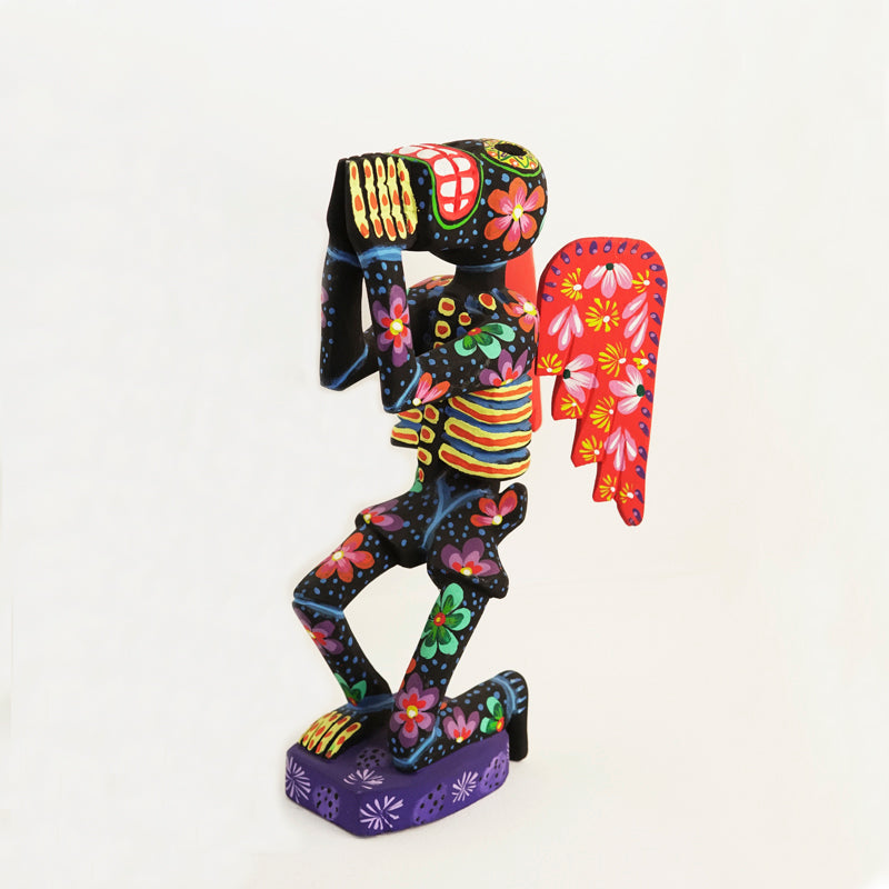 Handmade colorfully painted pine wood standing skeleton figurine with removable wings. The base is purple and the skeleton is multi-colored and kneeling and clasping its hands together as if in prayer.