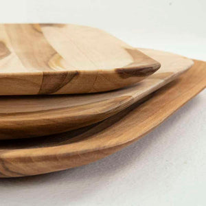 side view of three sizes of wood serving boards made of teak