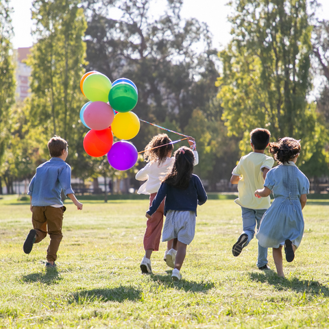 children running and playing with a balloon