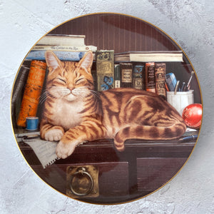 "Royal Doulton decorative plate ""Meet Marmaduke"" cat with a shelf of cat themed books."